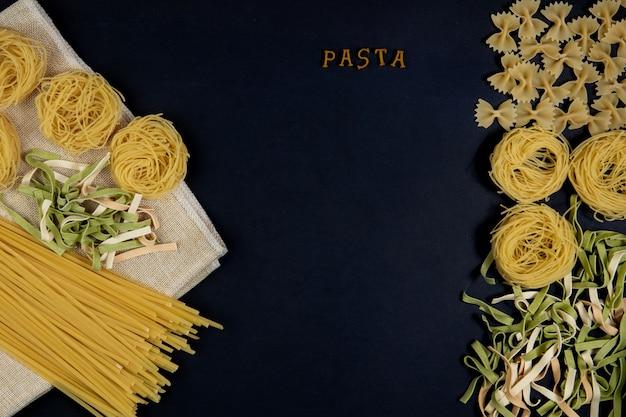 Verschiedene nudelmischungen auf dunklem hintergrund, metalllöffel. lebensmittelkonzept. das wort pasta italienisches essen und menükonzept.