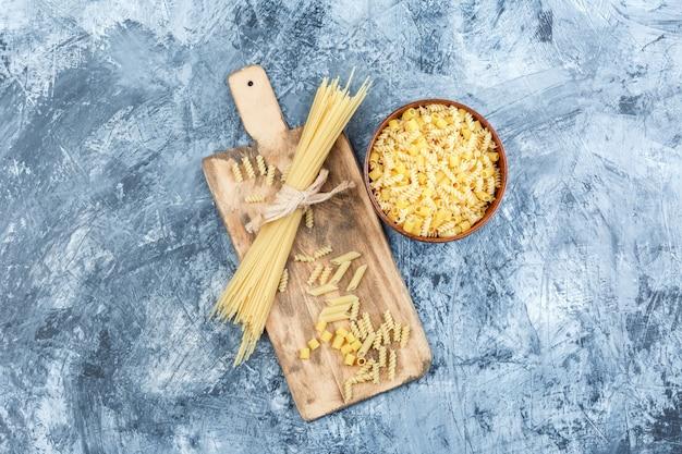 Verschiedene nudeln in einer schüssel mit spaghetti-draufsicht auf einem grauen gips- und schneidebretthintergrund