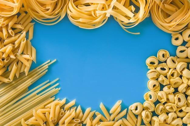 Verschiedene nudelsorten. ravioli penne pasta tortellini und capellini rahmen auf blauem hintergrund