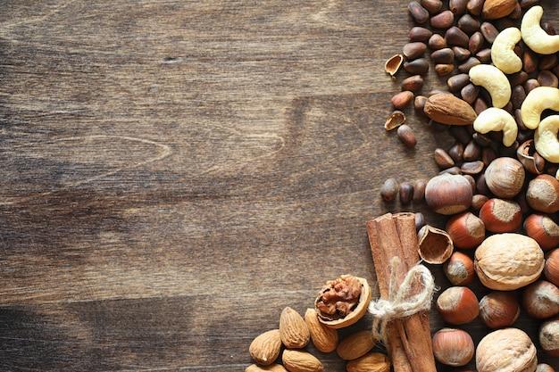 Verschiedene nüsse auf einem holztisch. zeder, cashew, haselnuss, walnüsse und ein löffel auf dem tisch. viele nüsse sind in der schale und chistchenyh auf einem hölzernen hintergrund
