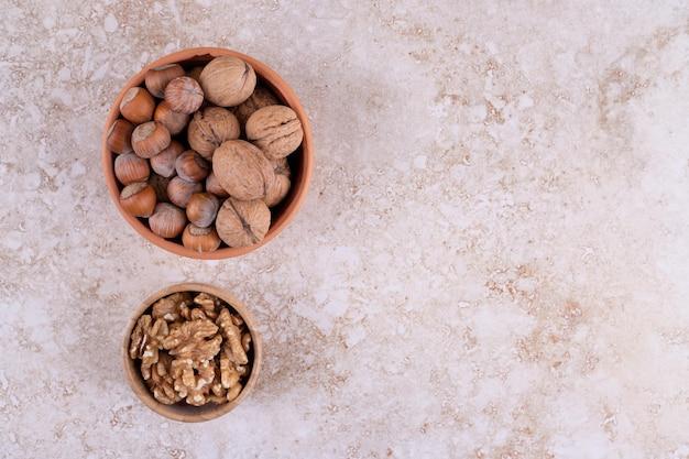 Verschiedene nüsse auf holzschale auf marmorhintergrund.
