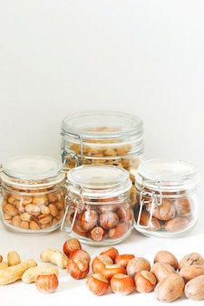 Verschiedene nüsse auswahl: haselnüsse, pistazien und pekannüsse im glas