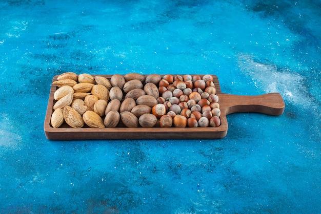 Verschiedene nüsse in einem brett, auf dem blauen tisch.