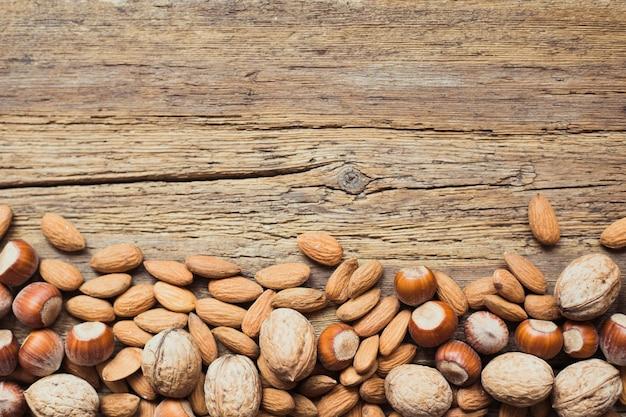 Verschiedene nüsse in einem hölzernen hintergrund