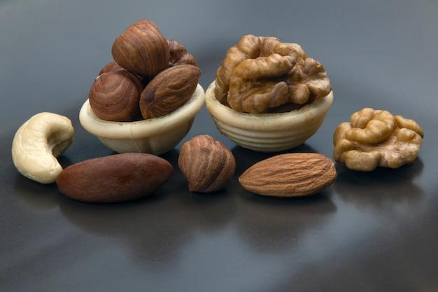 Verschiedene nüsse in einem waffelkorb auf einem grauen tisch. vitamin gesunde nahrung.