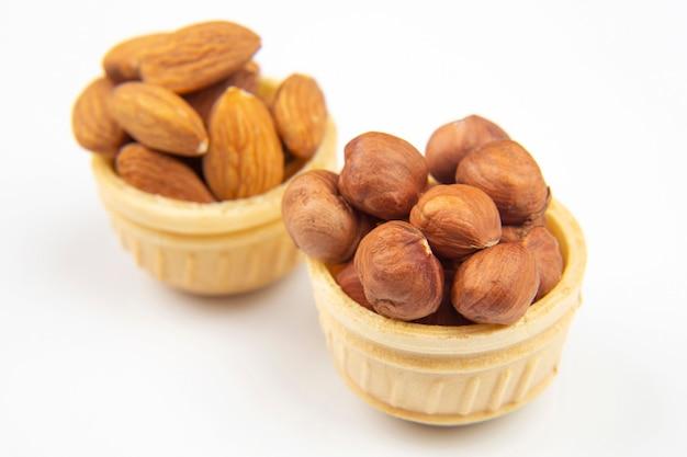 Verschiedene nüsse in einem waffelkorb auf einem weißen hintergrund. vitamin gesunde nahrung.