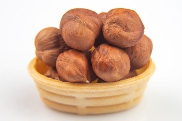 Verschiedene nüsse in einem waffelkorb auf einem weißen