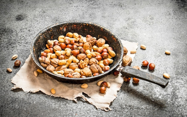Verschiedene nüsse in einer pfanne auf rustikalem hintergrund