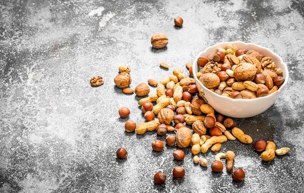 Verschiedene nüsse in einer schüssel auf rustikalem hintergrund