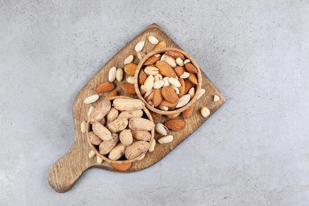 Verschiedene nüsse in holzschalen und auf holzbrett auf marmorhintergrund gestapelt. hochwertiges foto