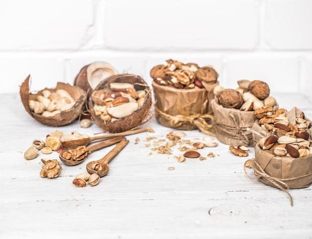 Verschiedene nüsse in platten und holzlöffel nahaufnahme auf weißem holzhintergrund, konzept der gesunden proteinkraft