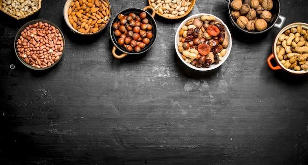 Verschiedene nüsse in schalen auf einer schwarzen tafel