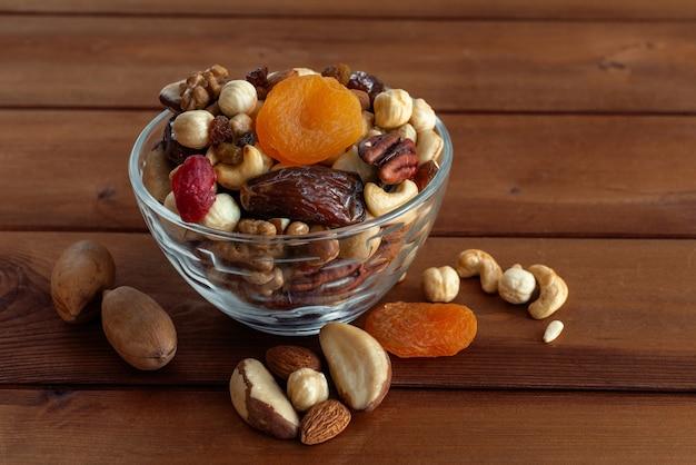 Verschiedene nüsse in schüssel auf holztisch. gesundes essen und snack. walnuss, pekannuss, mandeln, haselnüsse, macadamia und cashewnüsse