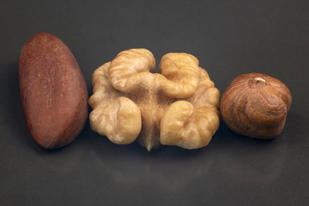 Verschiedene nüsse nahaufnahme auf einem grauen hintergrund. gesunde ernährung und vitamine