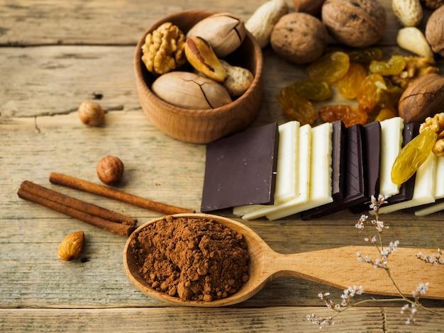 Verschiedene nüsse, schokolade und trockenfrüchte, zimt und kakao auf einem holztisch