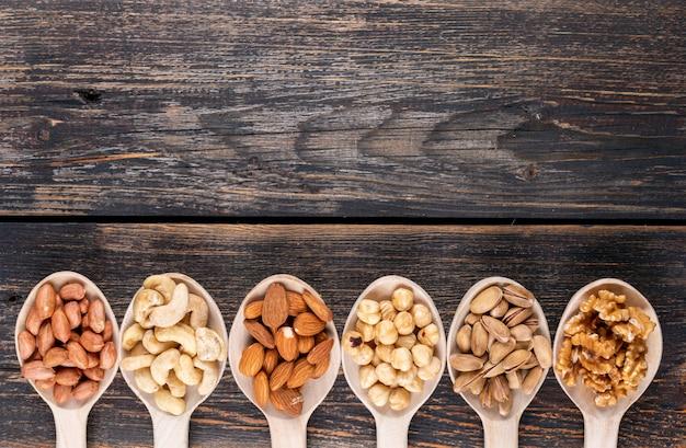 Verschiedene nüsse und getrocknete früchte in einem holzlöffel mit pekannuss, pistazien, mandel, erdnuss, cashew, pinienkernen draufsicht