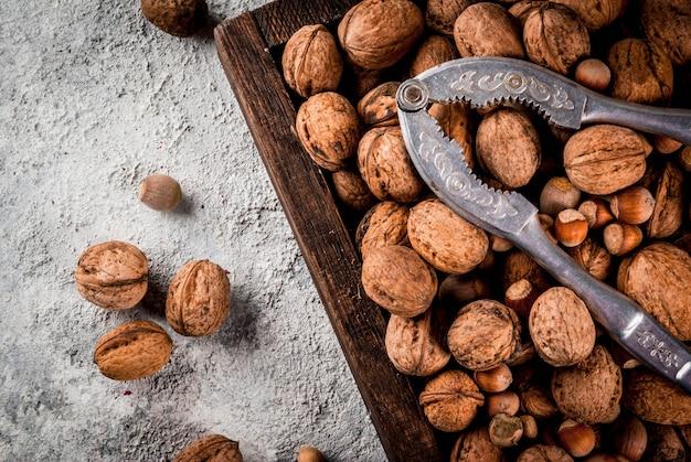 Verschiedene nüsse und nussknacker in der holzkiste. auf rustikalem grauem steintisch