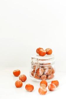 Verschiedene nüsse zur auswahl: haselnüsse, pistazien und pekannüsse in gläsern