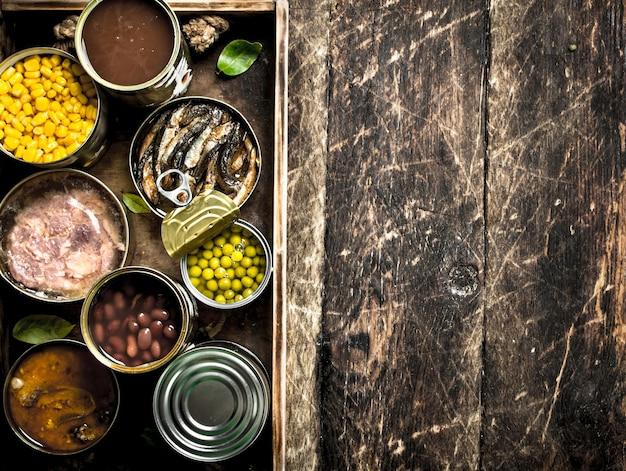 Verschiedene obst-, gemüse-, fisch- und fleischkonserven in blechdosen auf altem tablett.