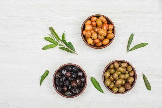 Verschiedene oliven in tonschalen mit olivenbaumzweig und draufsicht auf weißem holz