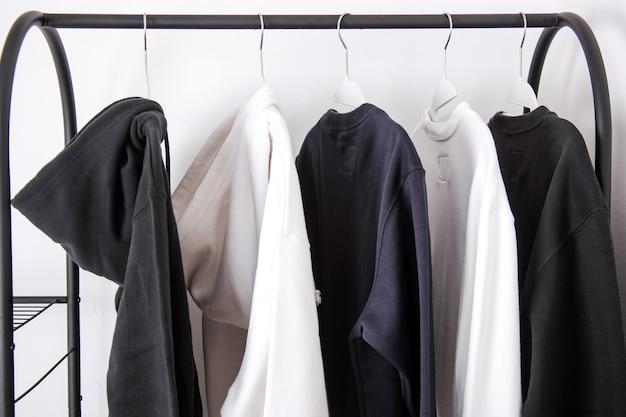 Verschiedene outwear wie hoodie und pullover hängen an kleiderbügeln