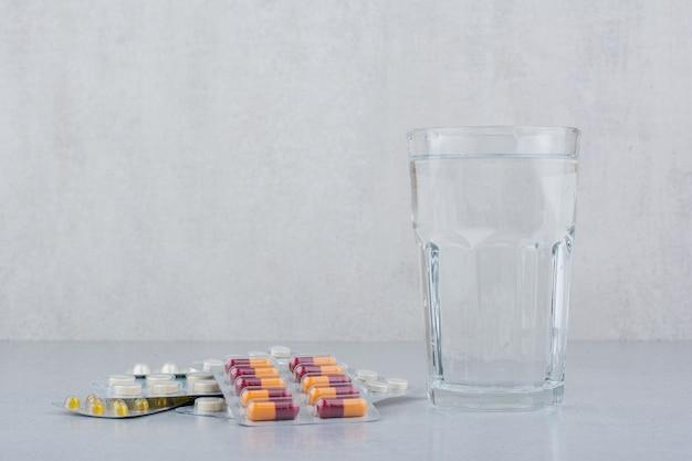 Verschiedene packungen mit kapseln und pillen mit einem glas wasser.