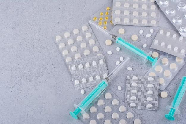 Verschiedene packungen mit medikamenten und leeren spritzen auf marmoroberfläche. foto in hoher qualität
