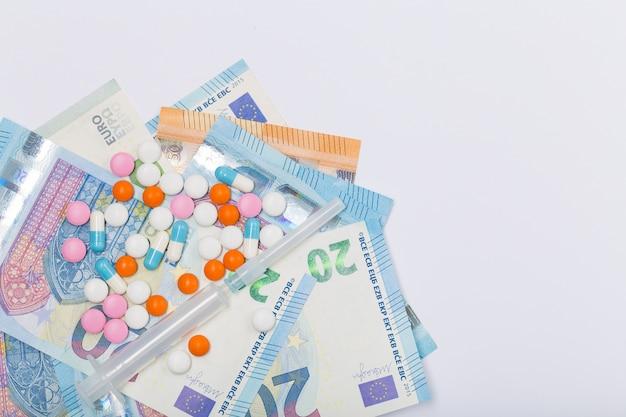 Verschiedene pharmazeutische medizinpillen, tabletten und spritzen auf eu-euro auf weißem hintergrund. gesundheitskonzept. krise. geld. freiraum. speicherplatz kopieren.