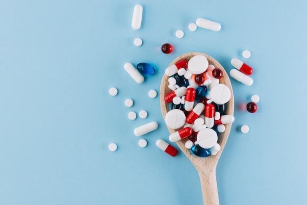 Verschiedene pillen auf holzlöffel