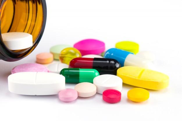 Verschiedene pillen, drogen und kapsel der medizin, die aus flasche auf weiß heraus gießen