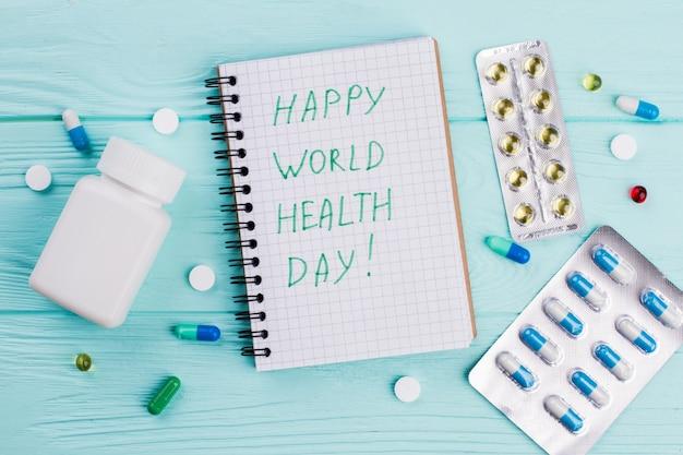 Verschiedene pillen mit notizbuch und blisterpackungen auf blauem hintergrund. herzlichen glückwunsch zum weltgesundheitstag.