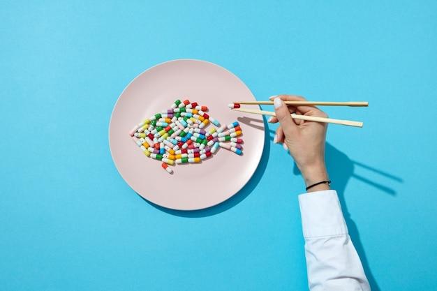 Verschiedene pillen und ergänzungen als fisch auf einem weißen teller essstäbchen in frauenhänden mit schatten auf einem blau. suppressiva für diätkonzept. draufsicht.