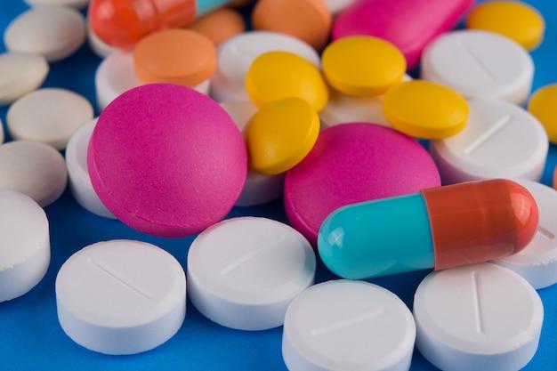 Verschiedene pillen und kapsel der medizin auf blau