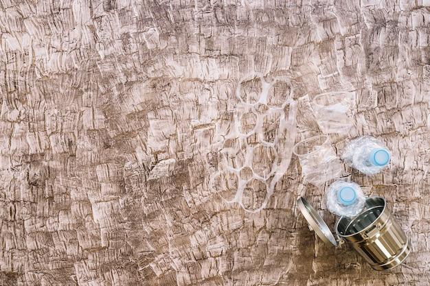Verschiedene plastikmaterialien über mülleimer gegen hölzernen hintergrund
