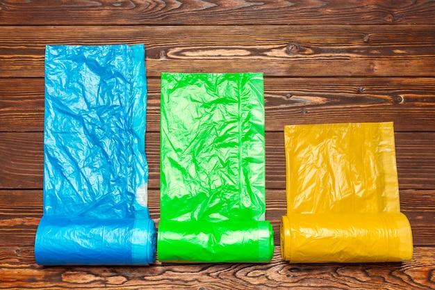 Verschiedene plastiktaschen auf hölzernem hintergrund.