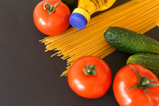 Verschiedene produkte. spaghetti, nudeln, tomaten, gurken und pflanzliches sonnenblumenöl.