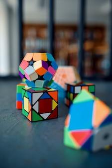 Verschiedene puzzlewürfel auf dem tisch, niemand. spielzeug für gehirn- und logisches denktraining, kreatives spiel, lösung komplexer probleme
