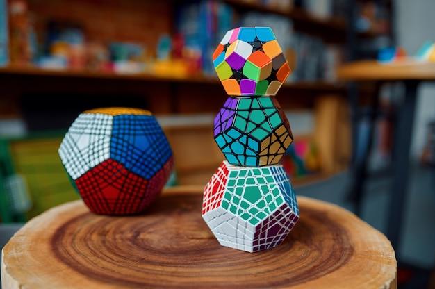 Verschiedene puzzlewürfel auf holzstumpf, detailansicht, niemand. spielzeug für gehirn- und logisches denktraining, kreatives spiel, lösung komplexer probleme
