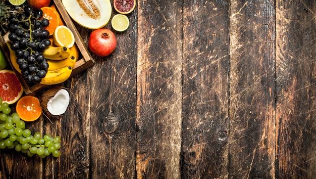 Verschiedene reife früchte in einer holzkiste auf holztisch.