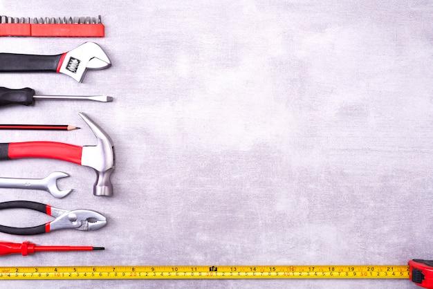 Verschiedene reparaturwerkzeuge auf grauem hintergrund. ausrüstung für den bau. werkzeugsatz reparieren. kopierbereich der draufsichtvorlage