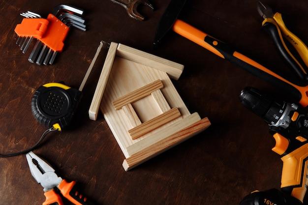 Verschiedene reparaturwerkzeuge und modell des hauses ausrüstung für den bau