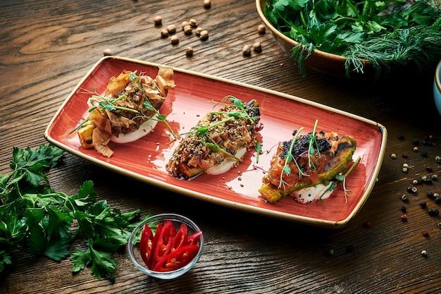 Verschiedene rinderfleisch-tataren mit verschiedenen belägen. vorspeisen vor dem hauptgericht auf einem teller auf einem holztisch. nahaufnahme, selektiver fokus