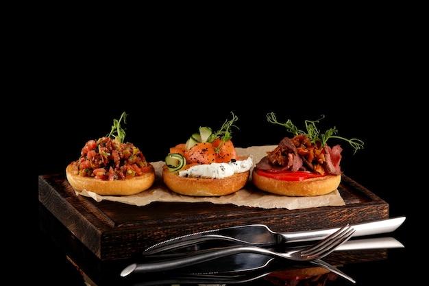 Verschiedene runde bruschetta mit verschiedenen füllungen (fleisch, gemüse, fisch). vielzahl von kleinen sandwiches.