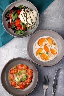Verschiedene salat-draufsicht. ceviche, buratta und kaki mit pinienkernen. verschiedene frische salate
