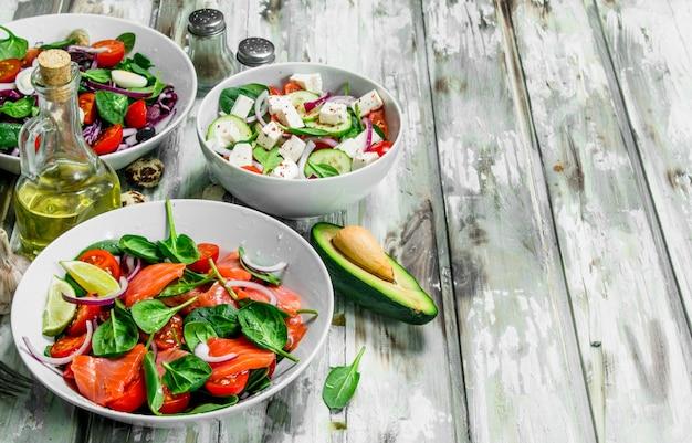 Verschiedene salate aus bio-gemüse, fisch und käse mit olivenöl und gewürzen.