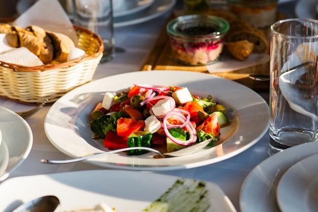 Verschiedene salate werden am festlichen tisch serviert.