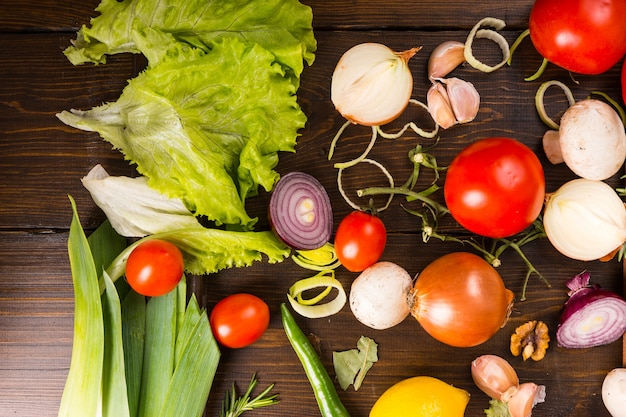 Verschiedene salatgrüns, tomaten, zwiebeln, paprika, gemischt mit walnuss und knoblauch, verteilt auf einem holztisch