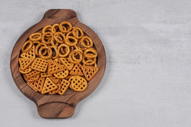 Verschiedene salzige cracker auf holzbrett.