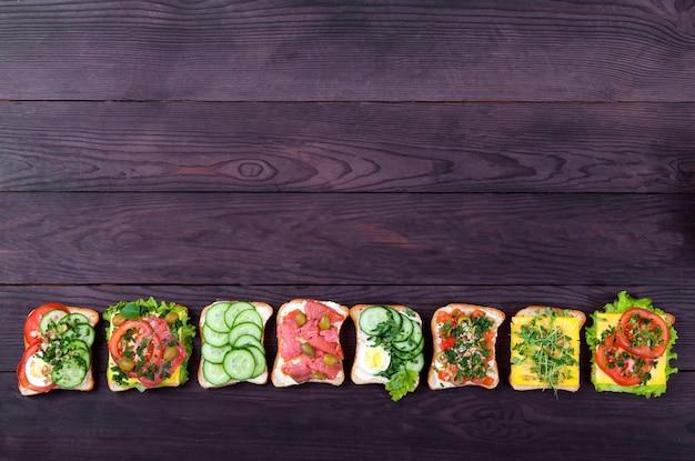 Verschiedene sandwiches auf toastbrot mit lachs, sprossen, gemüse, ei liegen in einer reihe auf einem braunen holz.