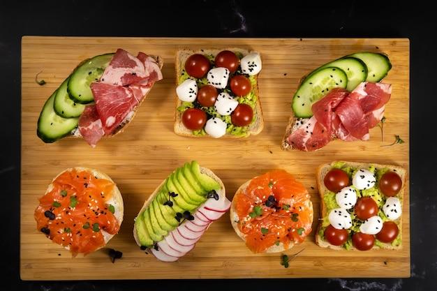 Verschiedene sandwiches mit fisch, käse, fleisch und gemüse auf dem brett liegend